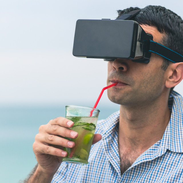 """Man with virtual reality goggles mobile device drinking cocktail outdoors on the beach with sea and sky in the background. Concept of online futuristic virtual lifestyle"" stock image"