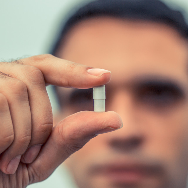 """""""Man holding medicine, capsule pill with blurred soft face in the background. Concept for making choice, medical care"""" stock image"""