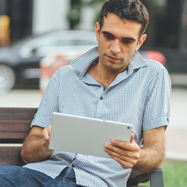 """""""Man sitting on a bench using technology browsing the net on his personal mobile device tablet. Concept for technology and humans."""" stock image"""