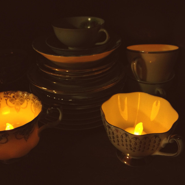 """Teacups on a shelf with tea lights glowing inside."" stock image"