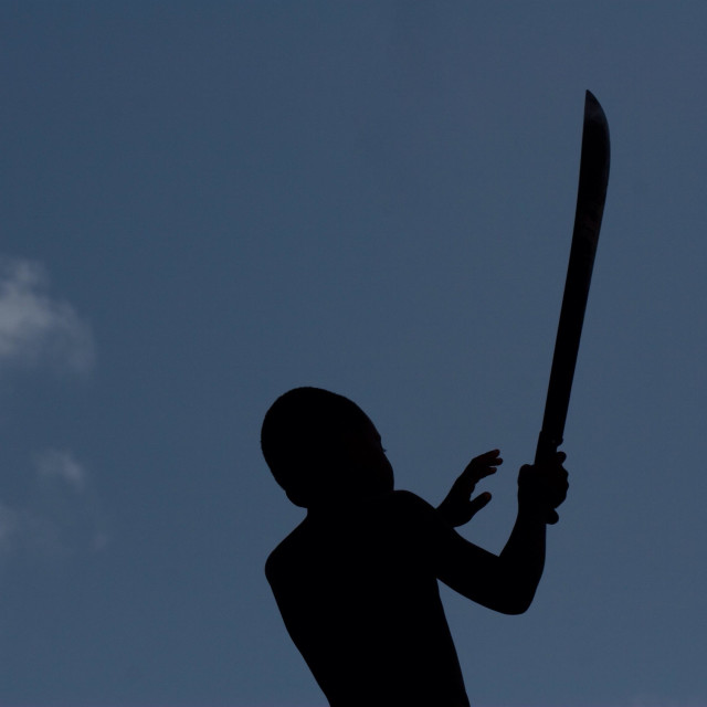 """""""A small boy wielding a large machete in Dominican Republic."""" stock image"""