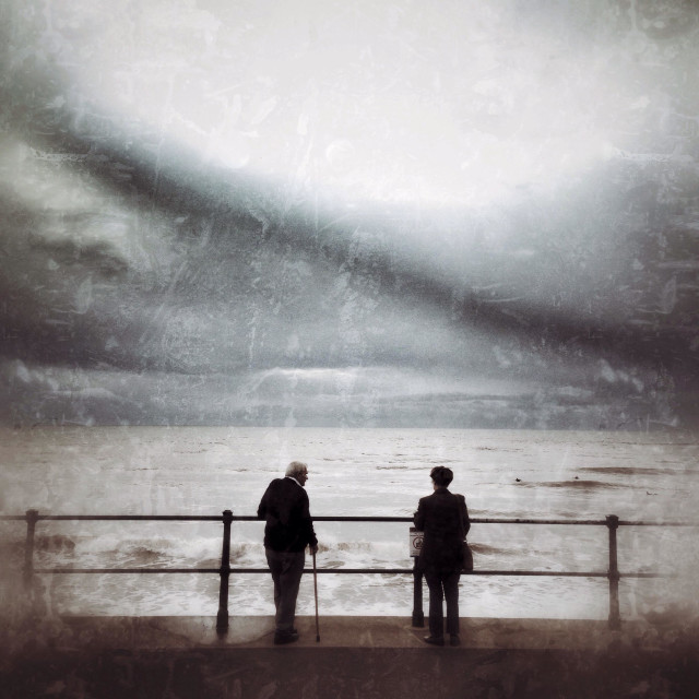 """""""Storm approaching as two elderly people watch at Sidmouth, Dorset"""" stock image"""