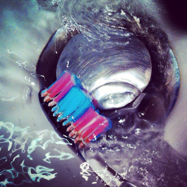 """Cleaning the toothbrush with water near the sinkhole"" stock image"
