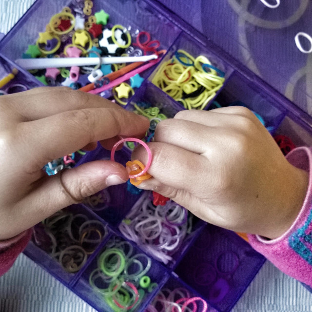 """""""Young girl making something with loom bands. POV image of hands loom banding."""" stock image"""