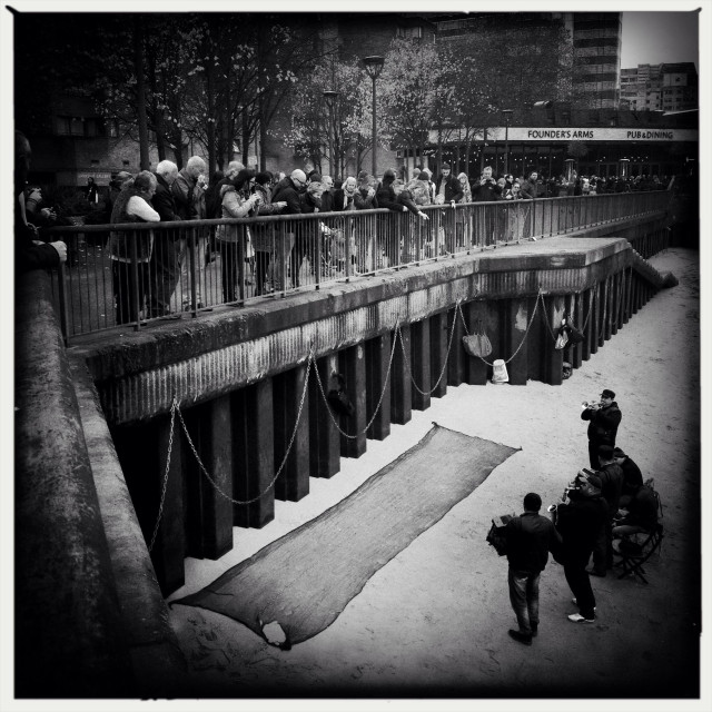 """""""Musicians performing at the riverbed of the Thames in London with a crowded audience consist of passer by people"""" stock image"""