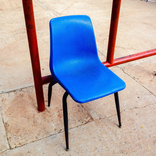 """""""Empty bright blue plastic chair on playground."""" stock image"""