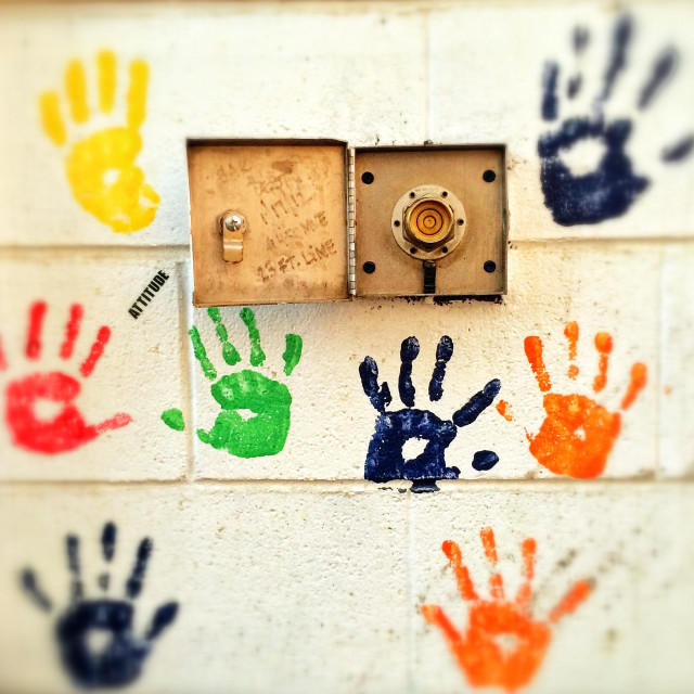 """Painted hands on a wall show an artistic flair."" stock image"