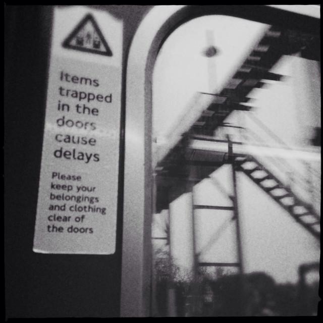 """Warning sign on tube door; rail/tube signals through window"" stock image"