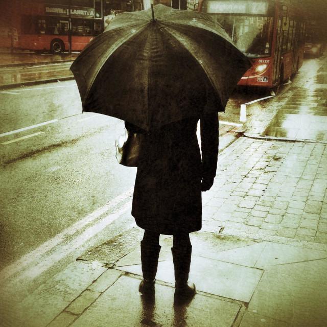 """Lady holding an umbrella in rainy London."" stock image"