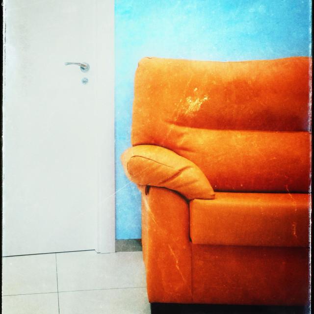 """Orange sofa, blue wall, white door and floor."" stock image"