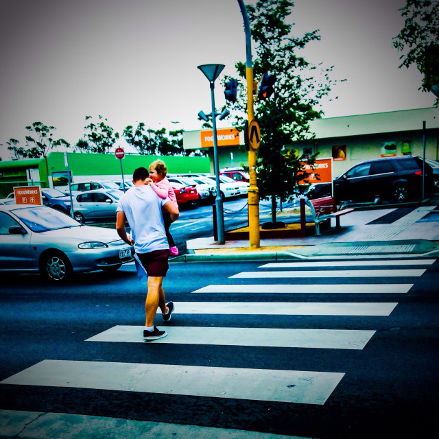 """""""A man holds his child in his arms as he crosses pedestrian crossing."""" stock image"""