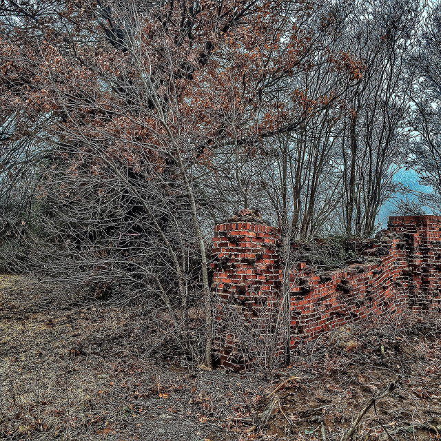 """Overgrown old cemetery brick wall in strong HDR"" stock image"