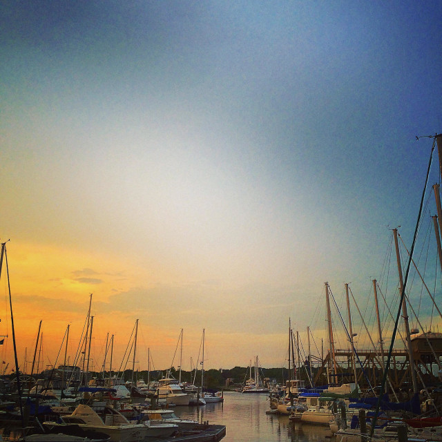 """""""Mystic, CT port full of sailboats and powerboats at sunset"""" stock image"""
