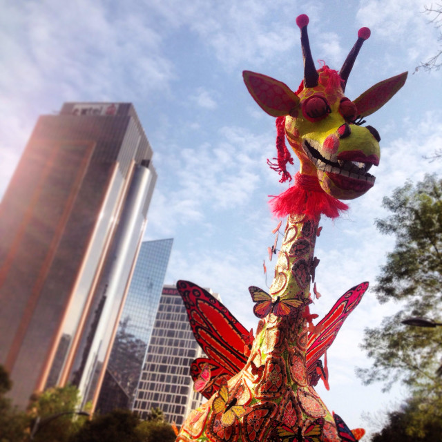 """giant paper mache sculpture of a winged giraffe and a skyscraper at the Alebrijes Monumentales Parade,Reforma Ave,Mexico City, Mexico. Art work called Girabrije by artist Enrique Luis Estrada Alfaro"" stock image"