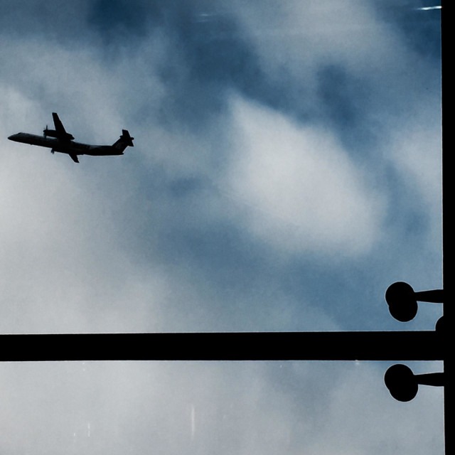 """""""A shot taken from the inside of an airport of an airplane taking flight into the sky"""" stock image"""