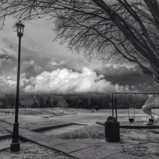 """Lamppost and trees frame a dramatic sky. Black and white"" stock image"