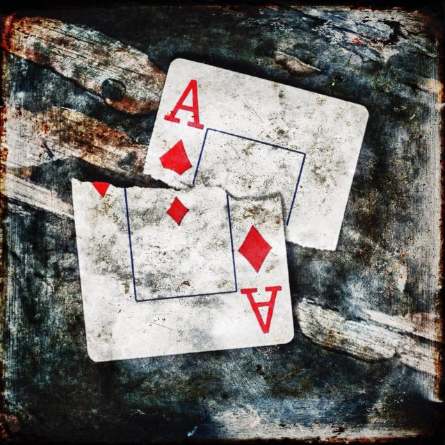 """The ace of diamonds from a deck of playing cards torn in half."" stock image"