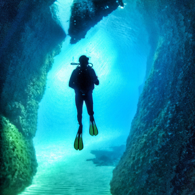 """""""Young male scuba diver swimming in a cavern and looking up"""" stock image"""