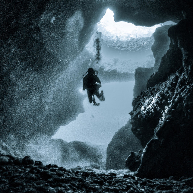 """""""Conceptual monochrome image of a young man scuba diving in the Blue Hole cavern"""" stock image"""