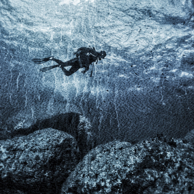 """""""Young male scuba diver swimming over rocky seabed"""" stock image"""