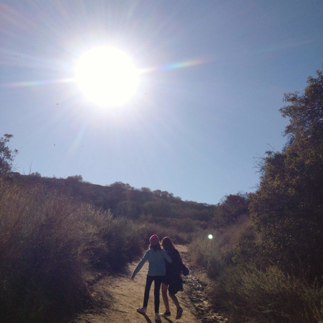 """Two young girls walk up a mountain path with the sun shining above them."" stock image"