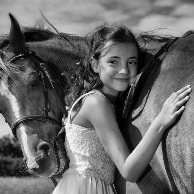"""""""A young girl cuddling her pet Pony."""" stock image"""
