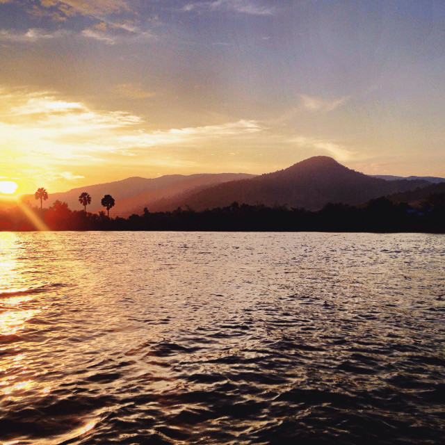"""The effulgent Sun sets over the Dâmrei Mountains (Elephant Mountains) and the Kampot River. Kampot, Cambodia."" stock image"
