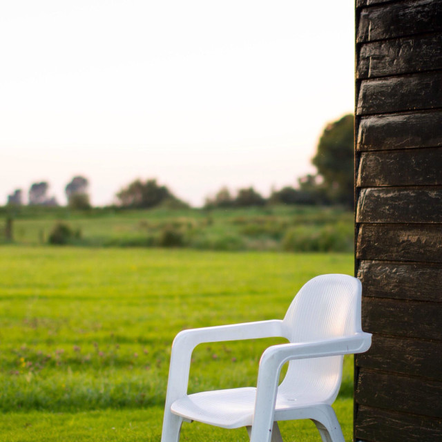 """""""White plastic chair up against the summer house in Holland"""" stock image"""