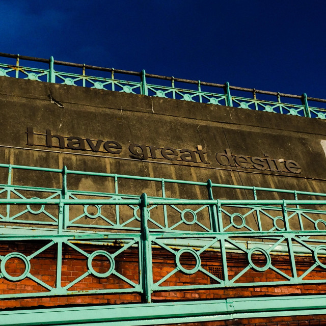 """""""Green railings at Brighton seafront with slogan """"I have great desire"""" in lettering on the sea wall"""" stock image"""