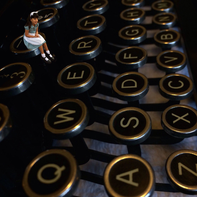 """""""Young girl dressed as Alice in Wonderland sitting on the key of an old fashioned Typewriter."""" stock image"""