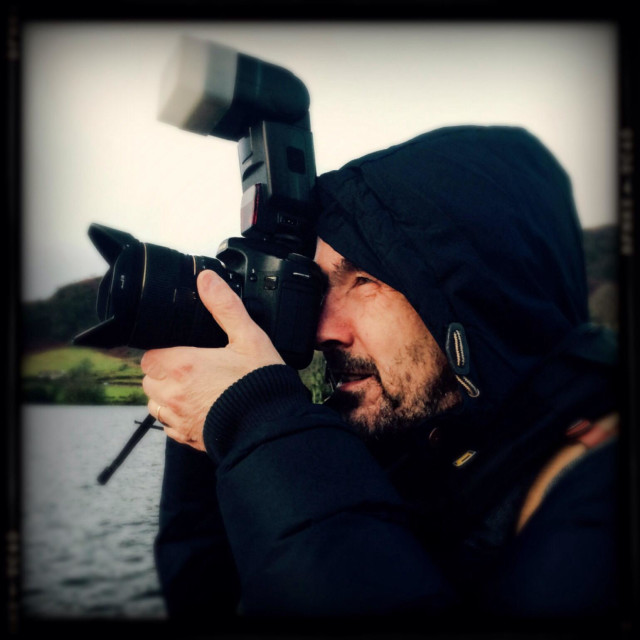 """""""Photographer in outdoor gear composing shot on DSLR"""" stock image"""