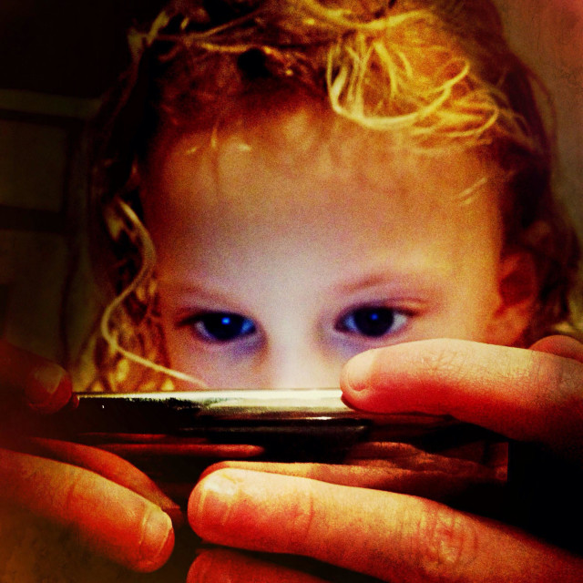 """""""Young girl playing on iPod with her face illuminated by screen"""" stock image"""