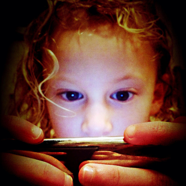 """""""Young girl playing game with her face illuminated by screen light"""" stock image"""