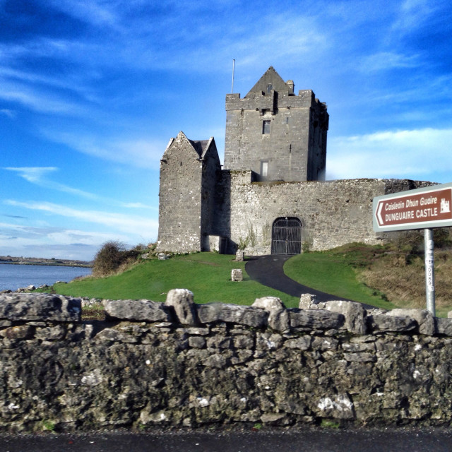 """Irish landscape, castle in a green field with a stone fence, the sea in the background, in a blue and slightly cloudy sky and a sunny day"" stock image"