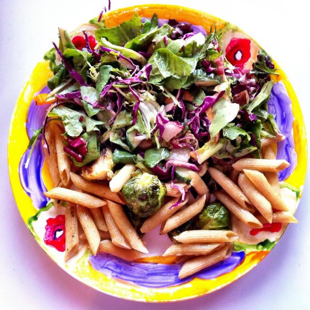 """Colorful vegan pasta dish with salad"" stock image"