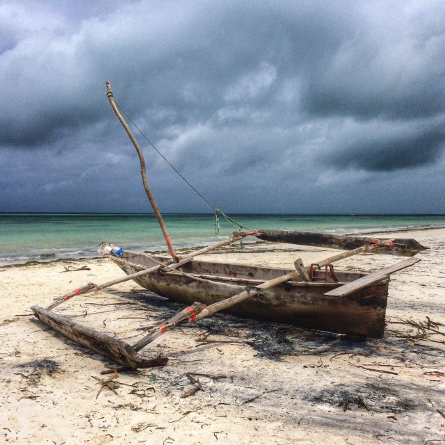 """Traditional fishing boat at the beach in Zanzibar, Tanzania."" stock image"