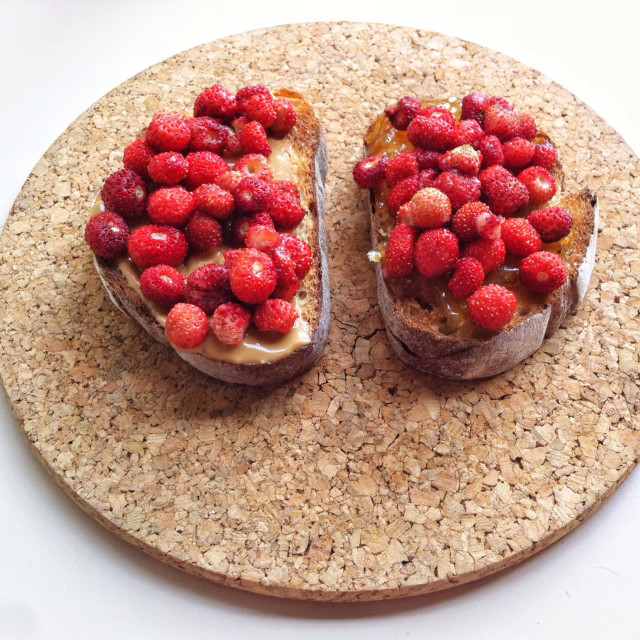 """""""Peanut Butter and wild strawberries sandwich on gray bread served on cork board"""" stock image"""