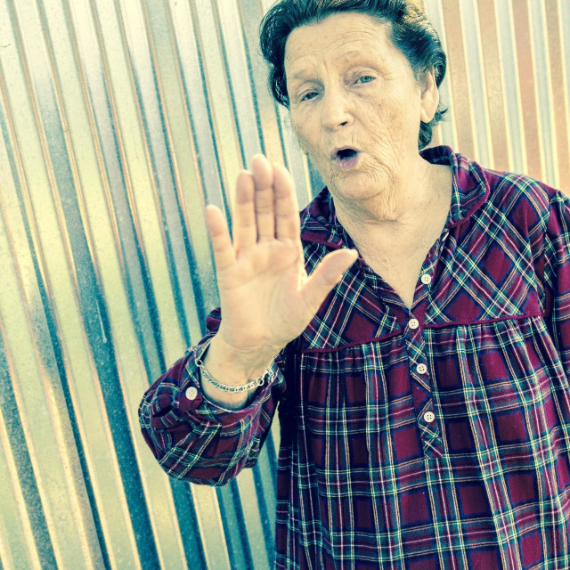 """""""A 78 year old woman holding her hand up as if saying, stop!"""" stock image"""