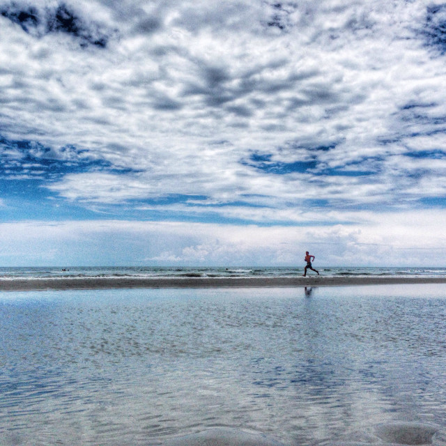 """""""Running on the beach with clouds reflecting in the water"""" stock image"""