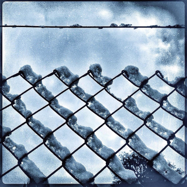 """Snow collected on a chain link fence in the middle of winter."" stock image"