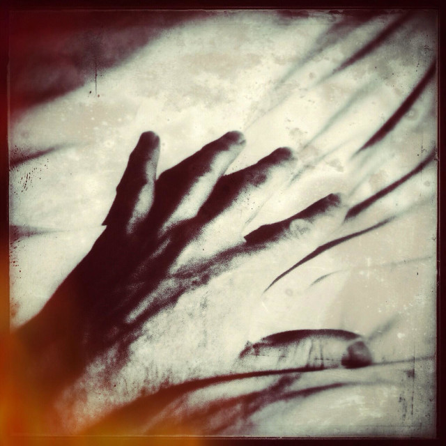 """""""Close up of a scary, sinister looking male hand reaching for something in the dark, with distressed overlay."""" stock image"""