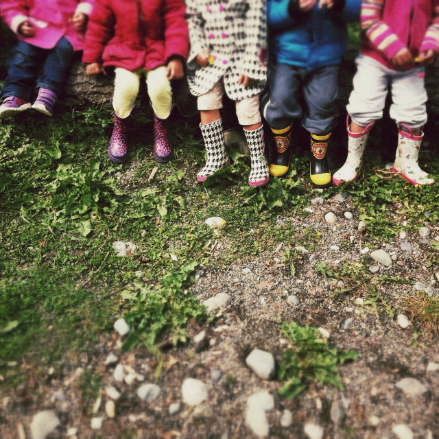 """""""Row of young children wearing rubber boots on a playground"""" stock image"""
