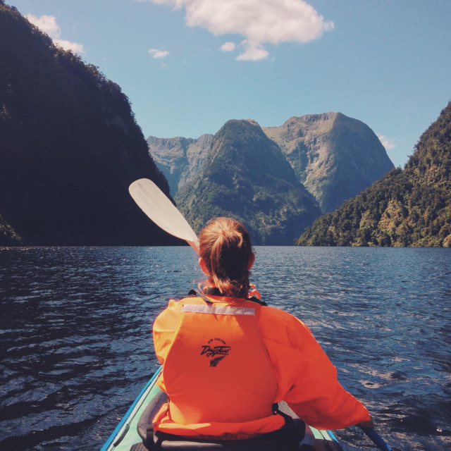 """""""A young woman kayaking in the fjords"""" stock image"""