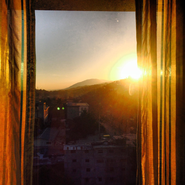"""Sunrise through a window in Port Au Prince, Haiti."" stock image"