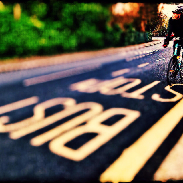 """""""Cyclist rides past bus stop, Harrow on the hill, North West London, England, United Kingdom, Europe"""" stock image"""