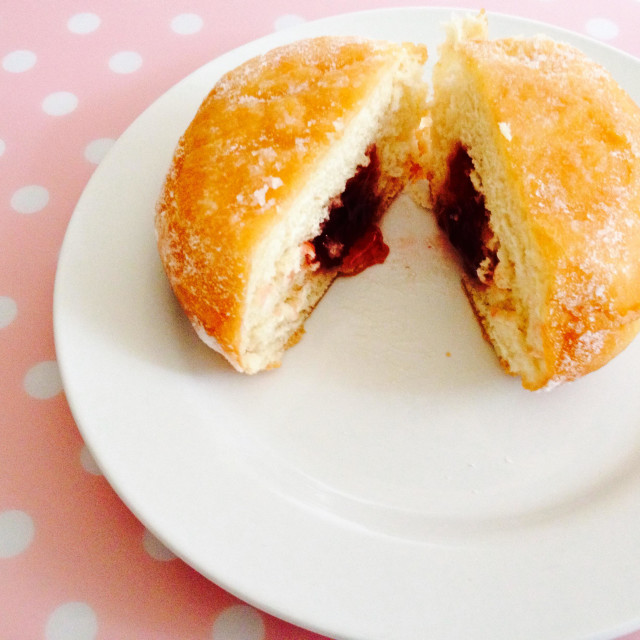 """Jam filled doughnut on a white plate"" stock image"