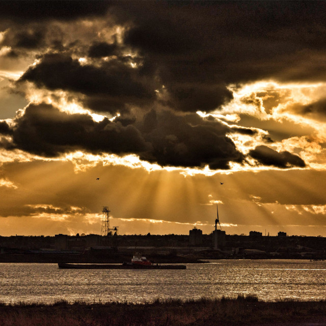 """""""A ship sails up the river Thames at Rainham Marshes, Essex, UK during a spectacular sunset."""" stock image"""