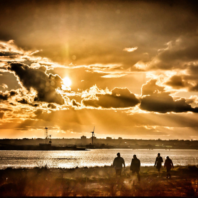 """""""Bird watchers walk beside the river Thames at RSPB Rainham Marshes during a spectacular winter sunset"""" stock image"""
