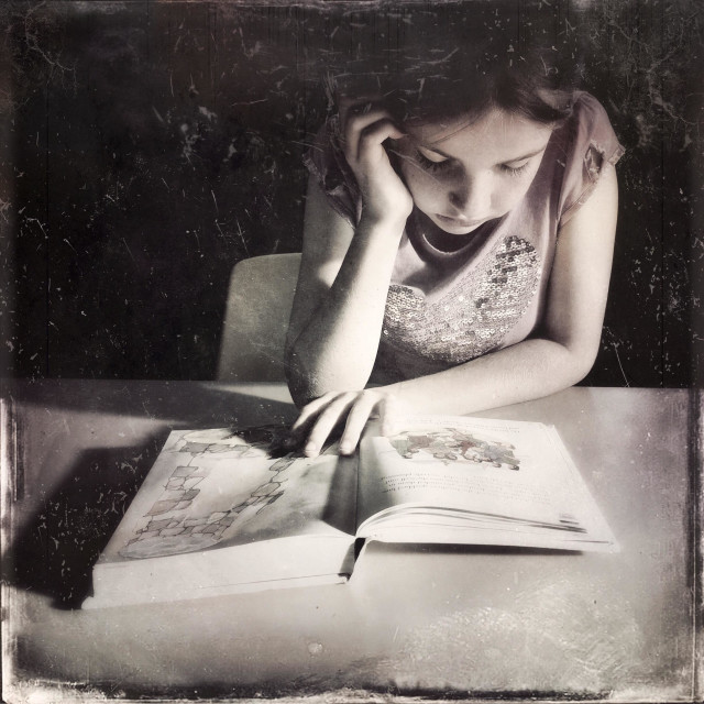 """""""Young girl absorbed in reading a book"""" stock image"""
