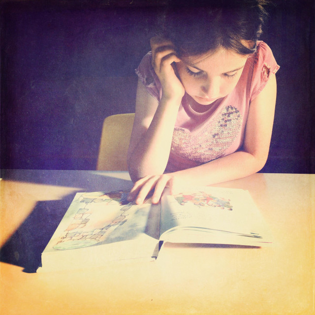 """""""Young girl absorbed in reading a book - vintage"""" stock image"""
